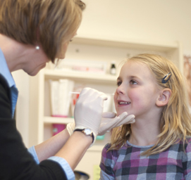 Study nurse Andrea Blom, RN, BSN, obtains an NP swab sample from five-year-old Lexi Frye at a surveillance visit.