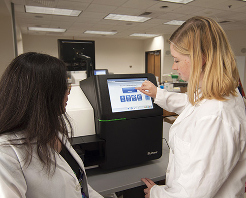 Dr. Baker and team member Anne Atkins, MPH, with the new DNA sequencing instrument, which can detect the gene mutations responsible for 97 percent of CF cases.