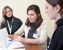 Genetic counselor Laura Birkeland, MS, CGC (left) observes first-year genetic counseling intern Sarah Hamilton (center) in the clinic.