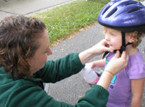 Pediatrics resident Jennifer Jones, MD, adjusts a rider's helmet.
