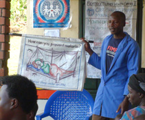 A community volunteer teaches patients about malaria prevention in the clinic waiting room.